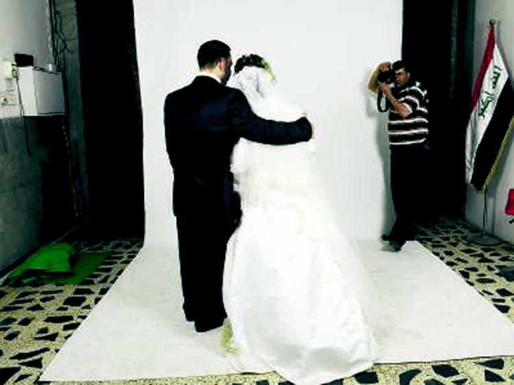 Onbekend bruidspaar op de rug gezien poseren voor een bruidsfotograaf